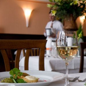 Ein Glas Weißwein auf gedecktem Tisch